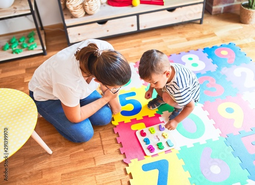 Obraz Beautiful teacher and toddler boy sitting on puzzle playing with numbers at kindergarten - fototapety do salonu