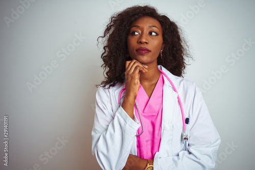 Fotomural  African american doctor woman wearing  pink stethoscope over isolated white background with hand on chin thinking about question, pensive expression