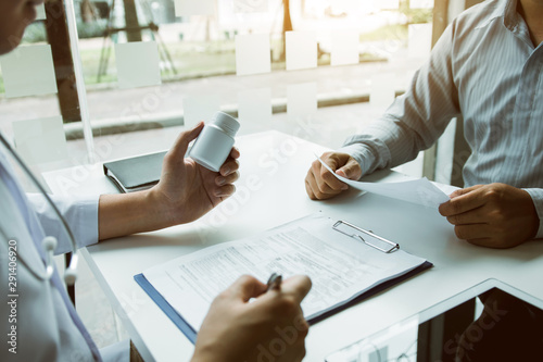 Fotografia  Confident doctor man holding a pill bottle and talking with senior patient and reviewing his medication at office room