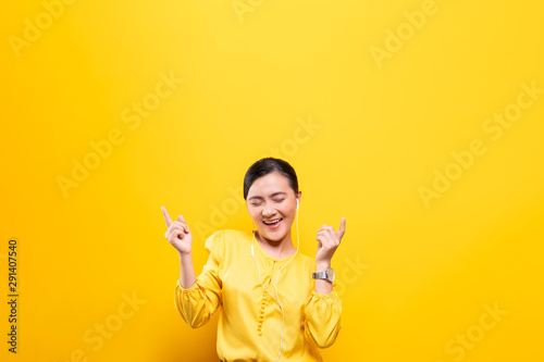 Woman with earphones listening music on isolated yellow background - 291407540