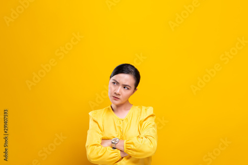 Valokuva  Angry woman standing isolated over yellow background