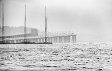 Oakland, San Francisco Bay Bridge During Early Morning Fog, Rain And Haze Over Rough Waters