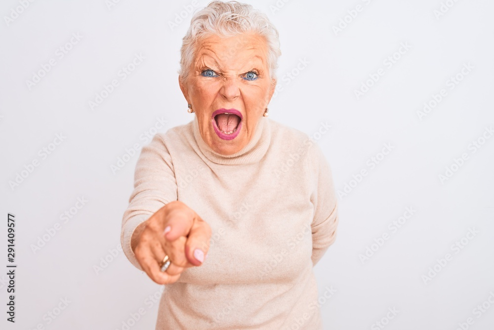 Fototapeta Senior grey-haired woman wearing turtleneck sweater standing over isolated white background pointing displeased and frustrated to the camera, angry and furious with you