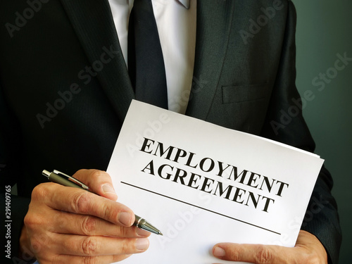 Photo sur Toile Amsterdam Man is holding Employment Agreement and pen.