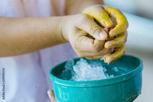 Close up to wash hands stained with yellow oil color by ice in a green bowl Canvas Print