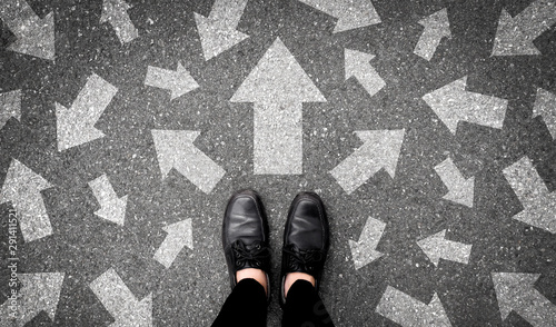 Obraz Selfie feet and arrows on road. Top view. Businessman in black shoes standing floor with many white arrow pathway sign choices. Future life with different direction symbol. Business success concept. - fototapety do salonu