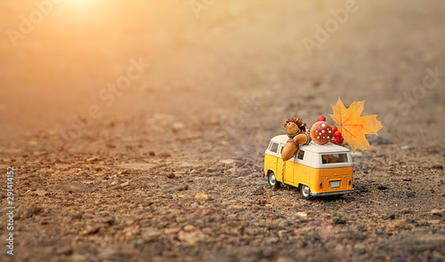 classic yellow bus on road. toy retro bus with maple leaf, cone, mushroom, acorn. autumn season concept. fall time. vacation adventure and travel concept. soft focus