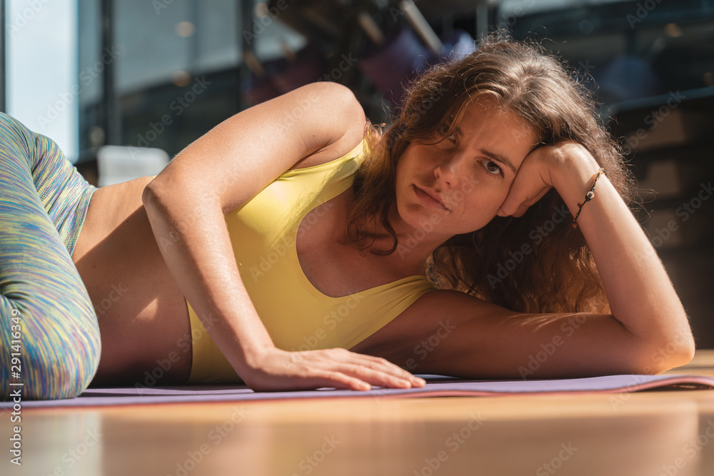 Fototapeta Portrait image of a woman wearing yoga clothes lying at a fitness facility