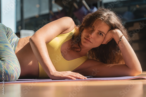 Portrait image of a woman wearing yoga clothes lying at a fitness facility - 291416349