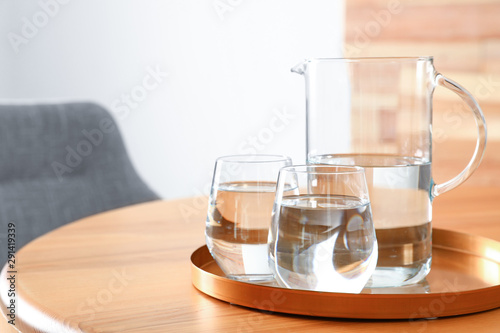 Obraz na plátně Tray with jug and glasses of water on wooden table in room, space for text