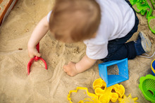 Little Kid Playing In Sand With Many Plastic Toys