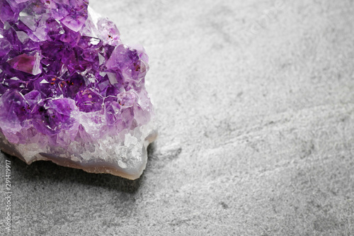 Photo Beautiful purple amethyst gemstone on grey table, space for text