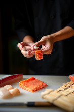 Closeup Of Chef Hands Preparing Japanese Food. Japanese Chef Making Sushi At Restaurant. Young Chef Making  Traditional Japanese Sushi On Cuting Board