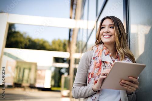 obraz lub plakat Beautiful brunette girl using tablet for work, freelance, blogging, studying, shopping