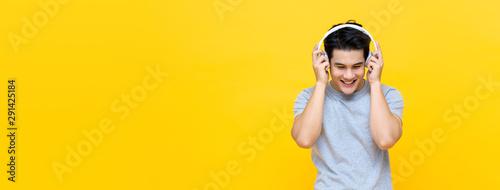 Happy Asian man wearing headphones listening to love song - 291425184