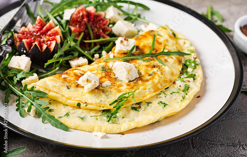 Poster Pays d Asie Omelette with feta cheese, parsley and salad with figs, arugula on white plate. Frittata - italian omelet.