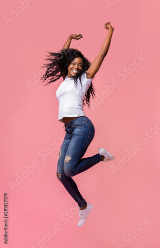 Smiling young african woman jumping in air Canvas Print