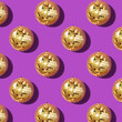 canvas print picture - New year baubles. Shiny gold disco balls on violet background. Pop disco style attributes, retro concept. Creative Christmas pattern. Flat lay, top view.