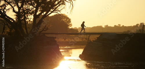 Okavango / Botswana - June 2016: Local crossing a bridge during sunrise in the wetlands of the Okavango Delta in Botswana, Africa Canvas Print