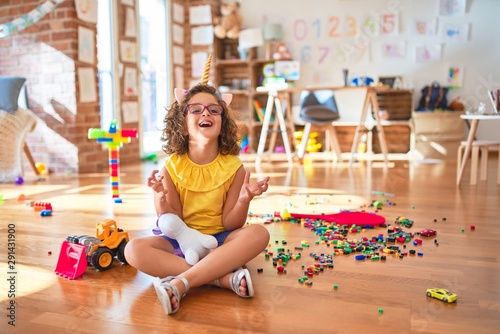 Valokuva Beautiful toddler wearing glasses and unicorn diadem sitting on the floor at kindergarten crazy and mad shouting and yelling with aggressive expression and arms raised