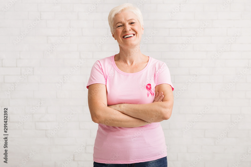 Fototapeta Senior Woman In Pink Breast Cancer T-Shirt Standing Over White Wall