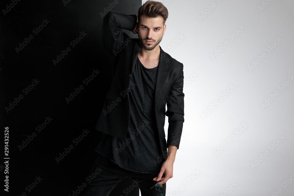 Fototapeta seductive young man holding sunglasses in studio