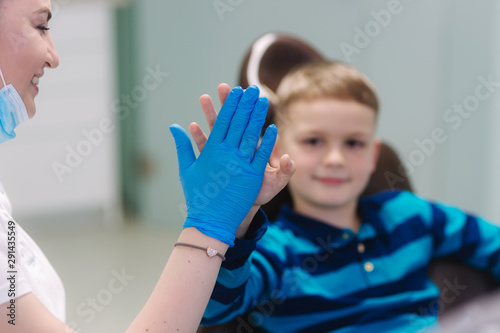 Stampa su Tela  Little boy give five to dantist at the clinic
