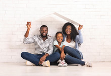 African American Family Sitting Under Roof Dreaming Of New Home.