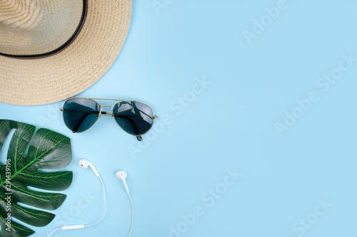 Fototapeta Traveler's vacation with hat and sunglasses on a blue background. Travel Concept. obraz na płótnie