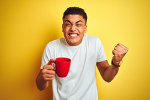 Young Brazilian Man Drinking Cup Of Coffee Standing Over Isolated Yellow Background Screaming Proud And Celebrating Victory And Success Very Excited, Cheering Emotion