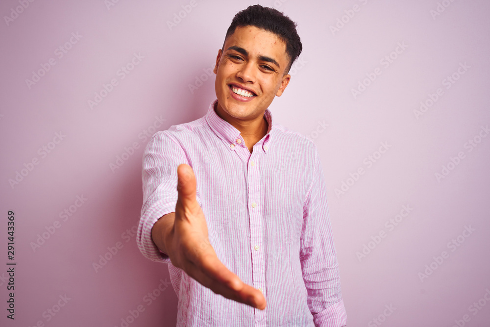 Fototapety, obrazy: Young brazilian man wearing shirt standing over isolated pink background smiling friendly offering handshake as greeting and welcoming. Successful business.