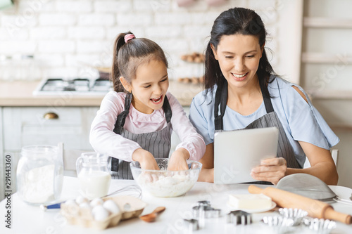 Cuadros en Lienzo Mother and daughter using digital tablet in kitchen, looking recipe