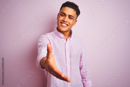 Young brazilian man wearing shirt standing over isolated pink background smiling friendly offering handshake as greeting and welcoming Canvas Print