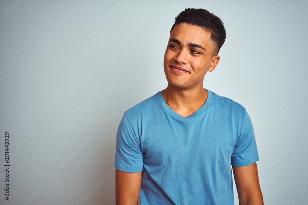 Fototapeta Young brazilian man wearing blue t-shirt standing over isolated white background smiling looking to the side and staring away thinking.