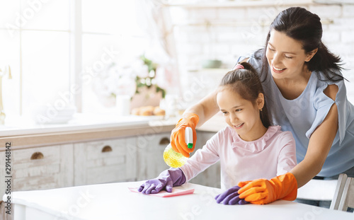 Obraz na plátně  Caring mom teaching daughter how to clean table with detergent
