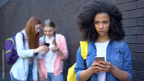 Photo  Sad african schoolgirl reading humiliating message, cyber bullying embarrassment