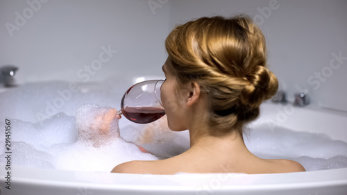 Fotomural  Adorable woman drinking wine in bath with foam bubbles, wellness and spa, relax