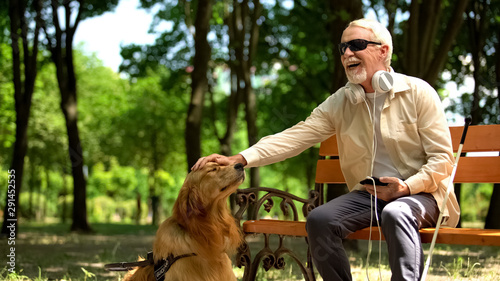 Photo sur Aluminium Magasin de musique Blind man with earphones stroking dog, full life of impaired, enjoying time