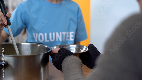 Fototapeta Female volunteer serving soup in shelter, care of poor people, charity project obraz