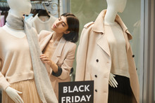 Portrait Of Beautiful Saleswoman Dressing Mannequins In Autumn Clothes While Setting Up Window Display For Black Friday Sale, Copy Space