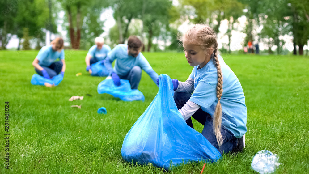 Fototapety, obrazy: School girl with group of eco volunteers picking up litter park, saving nature