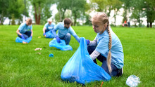 School Girl With Group Of Eco Volunteers Picking Up Litter Park, Saving Nature