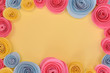 Pink, yellow and blue rose flat lay frame with crafted paper flowers around edges and empty light yellow copy space in middle