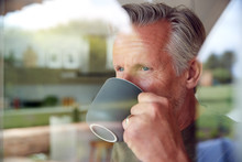 Senior Man Standing And Looking Out Of Kitchen Door Drinking Coffee Viewed Through Window