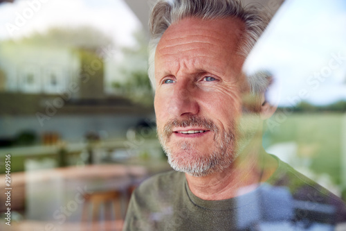 Senior Man Standing And Looking Out Of Kitchen Door Viewed Through Window Canvas Print