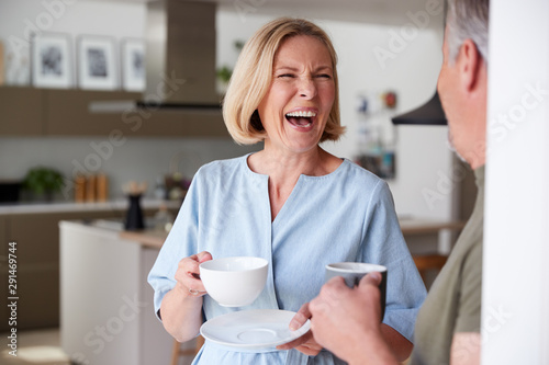 Senior Couple Standing At Home In Kitchen Drinking Morning Coffee Together Tableau sur Toile