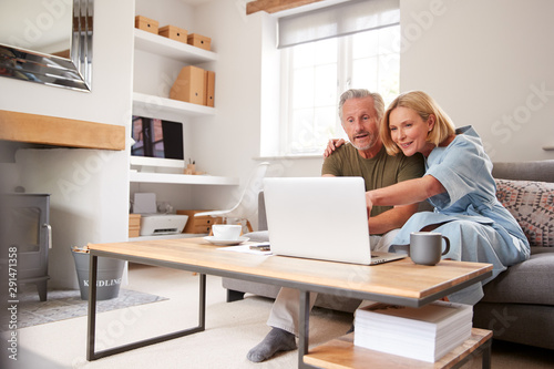 Photographie  Senior Couple Sitting On Sofa In Lounge At Home Using Laptop Together