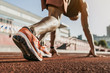 Leinwanddruck Bild - Close up of male athlete getting ready to start running on track . Focus on sneakers