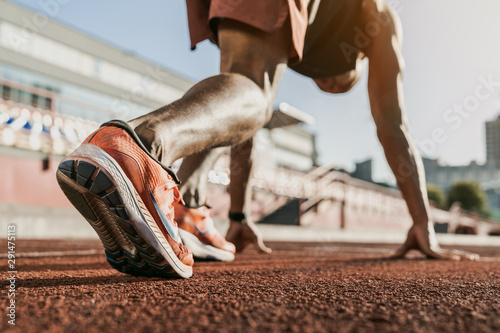 Photo Close up of male athlete getting ready to start running on track
