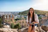 Fototapeta Big Ben - Junge Touristin auf Sightseeing Tour sitzt auf der Akropolis von Athen und liest in einem Reiseführer